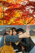 Three women take a souvenir photograph of themselves in front of colourful autumn leaves in Kyoto Japan