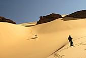 Touareg look at tourist slipping in dune  Oued Tin Tarabine Tassili Ahaggar  Sahara desert  Algeria