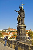 Tourist by statue of John the Baptist on Charles Bridge central Prague Czech Republic EU