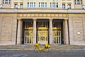 Postal bicycle in front of a building along Karl Marx Allee avenue in east Berlin Germany EU