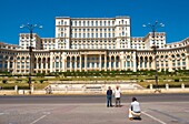 Tourists taking a photo in front of Palace of Parliament building in Bucharest Romania Europe