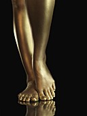 Woman legs covered with gold  Isolated on black background