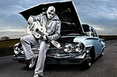 Rock´n´roll symbol Silver Elvis with a guitar sitting on a broken down classic car with open hood  Performing artist Peter Jarvis from Toronto Canada