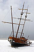 Rusting grounded ship in frozen water under dramatic sky wintertime scenic