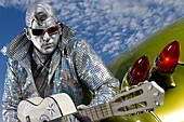 Rock´n´roll symbol Silver Elvis with a guitar propping on futuristic looking retro car under blue sky  Performing artist Peter Jarvis from Toronto Canada