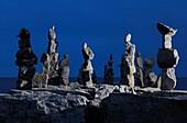 Stone human figures illuminated at night on a shore of lake Ontario in Toronto Inukshuk Inuit culture Spiritual symbol Atmospheric dramatic nighttime scenery