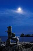 Stone human figure under moonlight on a shore of lake Ontario in Toronto Inukshuk Inuit culture Spiritual symbol Atmospheric dramatic nighttime scenery