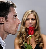 Young handsome man with a red rose standing in front of a woman in the background