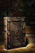Closeup of rustic ancient book with hard ornamental leather cover illuminated in darkness Artistic dramatic still life