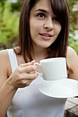 one young woman drinking coffee outdooe