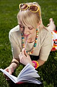 one young woman reading book on the grass outdoor in summer