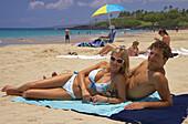 Young couple sunbathing on the beach, Hapuna State Recreation Area, Big Island, Hawaii, USA, America