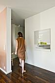 Woman walking through modern living area, Hamburg, Germany