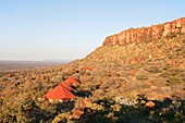 Namibia - The secluded chalets of the Waterberg Plateau Lodge just below the red sandstone rocks of the Waterberg Plateau Waterbeg Plateau Park, Namibia