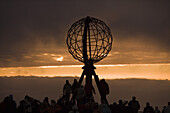 People at Nordkapp Globe Sculpture with Midnight Sun, North Cape, Finnmark, Norway, Europe