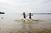 Zwei Kinder laufen ins Wasser, Sommerferien, Motala, Östergötland, Schweden.
