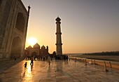 Tourists wait in line on the marble floor to enter the inside of the Taj Mahal, Agra, India as the sun sets over the western mosque