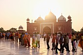 The sun sets over the western Mosque as tourists wait in line on the marble floor to enter to inside of the Taj Mahal, Agra, India