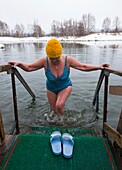 Woman emerging from cold lake at Ozerki hot springs in Petropavlovsk-Kamchatsky in Kamchatka penninsula Russia