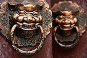 Detail of ornate door handles on door in Beijing alleyway called a hutong