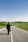 Businessman Walking Along an Isolated Country Road, Rear View