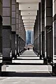 Businessman walking past columns of modern office area