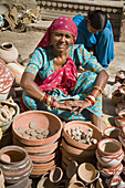 Woman selling pottery in a street, Bikaner, Rajasthan, India