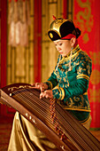 Mongolia, Ulaan Baatar. The Tumen Ekh Folk and Dance Group. Young girl playing antique instrument