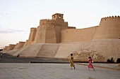 Adult, Adults, Architecture, Asia, cities, city, Color, Colour, Daytime, Ethnic, Ethnicity, exterior, female, Full body, Full length, Full-body, Full-length, Historic, Historical, History, Horizontal, human, Khiva, Khwarezm, outdoor, outdoors, outside, Pa