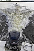 speedboat going to full power with huge wake and pulling waterskiier into the upright postition vertical