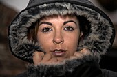 pretty irish brunette with brown eyes closes up fake fur coat against the cold and wet weather