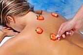Young woman receiving a beauty treatment with natural strawberries