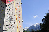 Artificial climbing wall on a bridge pillar above the river Inn with mountains in the background, Funpark Area 47, Oetztal valley, Tyrol, Austria
