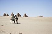 Camel rider in front of pyramids of Napata, Karima, Sudan, Africa