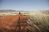 Off road vehicle on red sand track, Hartmann Valley, Namibia, Africa
