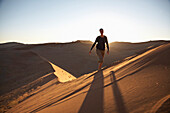 Woman walking over red sand dune, Namib Naukluft Park, Sossusvlei, Namibia, Africa