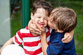 Boy (6 - 7 years) kissing friend's cheek