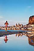 Jogger at beach,  old town, cathedral and cliff La Rocca, Cefalú, Palermo, Sicily, Italy
