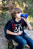 backpack, bottle, boy, break, break-time, brown hair, Caucasian ethnicity, chestnut hair, child, childhood, Color image, contemporary, country, day, drink, drinking, hike, hiking, human, infancy, kid, leisure, Male, one, one person, outdoor, pause, people