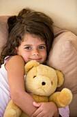 Caucasian girl hugging her teddy bear
