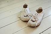 A pair of old plimsolls on a white wooden floor