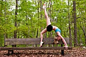 A young blond woman doing a yoga back bend posture on a wooden bench in a park.