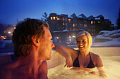 Woman and man bathing in outdoor pool, Four Seasons Resort Whistler, Whistler, British Columbia, Canada