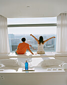 Couple enjoying view out of a hotel room, Madrid, Spain