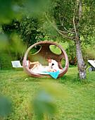 Couple relaxing in the garden, of an organic Hotel, Hirschegg, Kleinwalsertal, Austria