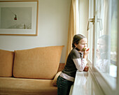 Girl looking out of the window, eating an apple, Hotel room, organic Hotel Chesa Valisa, Hirschegg, Kleinwalsertal, Austria