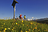 People with mountain bikes having a rest at Winklmoos alp in front of Loferer Steinberge, Reit im Winkl, Bavaria, Germany, Europe
