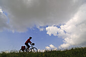 Cyclist beneath clouds at Campo Imperatore, Gran Sasso National Park, Abruzzi, Italy, Europe