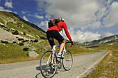 Cyclist at Campo Imperatore, summit of Corno Grande, Gran Sasso National Park, Abruzzi, Italy, Europe