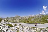 Cyclist on lonesome country road, Castel del Monte, Campo Imperatore, Abruzzi, Italy, Europe